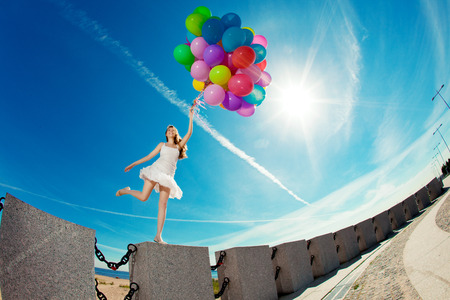 Happy birthday woman against the sky with rainbow-colored air balloons in her hands. sunny and positive energy of urban street. Young beautiful girl on the grass in the city photo