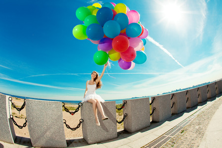 Happy birthday woman against the sky with rainbow-colored air balloons in hands. sunny and positive energy of urban street. Young beautiful girl on the grass in the city.  photo