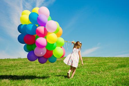Šťastné holčička drží barevné balónky. Dítě hraje na zelené louce. Usmívající se dítě. Reklamní fotografie