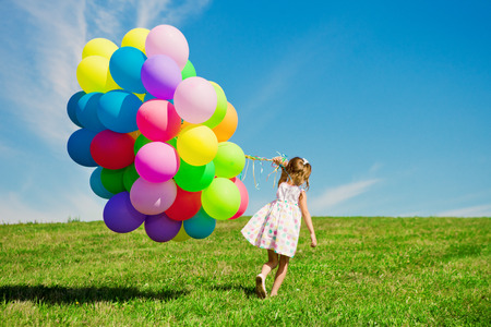 Happy little girl holding colorful balloons. Child playing on a green meadow. Smiling  kid.  Фото со стока