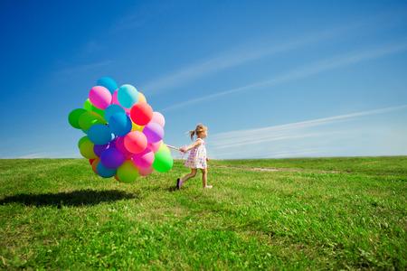 다채로운 풍선을 들고 행복 한 작은 소녀. 아이 녹색 초원에서 연주입니다. 웃는 아이. 스톡 콘텐츠