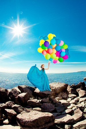 Luxury fashion woman with balloons in hand on the beach against the sky and the sun in long dress photo
