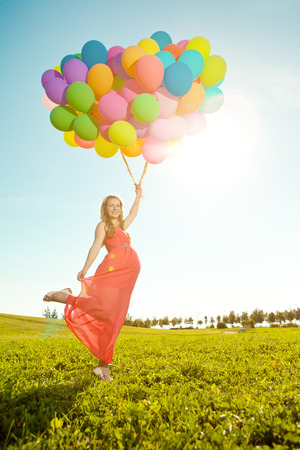 Young healthy beautiful pregnant woman with balloons outdoors. A girl with a tummy on the grass. Enjoyed by nature. photo
