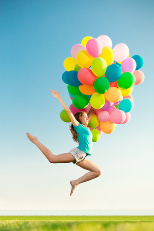 Happy birthday woman against the sky with rainbow-colored air balloons in hands. sunny and positive energy of nature. Young beautiful girl on the grass in the park.  photo