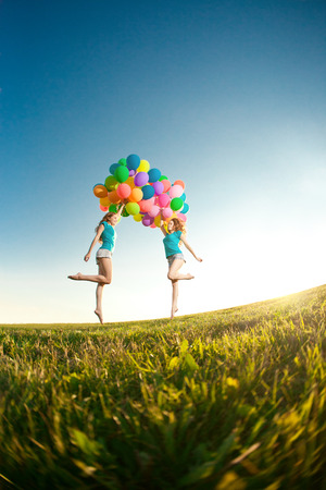 Happy birthday women against the sky with rainbow-colored air balloons in her hands.  sunny and positive energy of nature. Young beautiful girls, twins on the grass in the  park.  photo