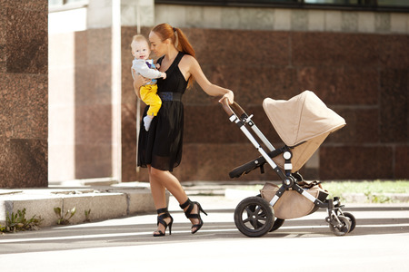 Fashionable modern mother on a city street with a pram. Young mother walks with a  child in the city. Beautiful young woman with a child in a baby carriage photo