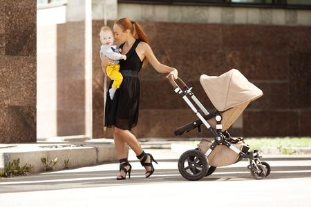 Modische moderne Mutter auf einer Straße mit einem Kinderwagen. Junge Mutter geht mit einem Kind in der Stadt. Schöne junge Frau mit einem Kind in einem Kinderwagen Standard-Bild - 26830708