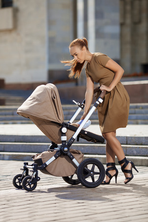 Trendy modern mother on a city street with a pram. Young mother walks with a child in the city. Beautiful young woman with a child in a baby carriage Stock Photo
