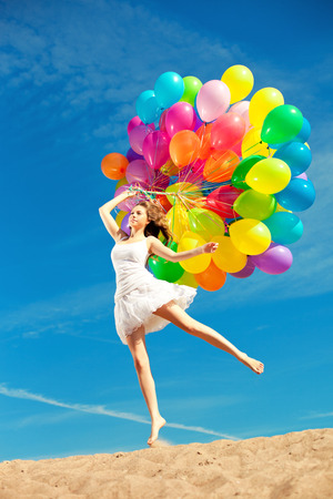 Beautiful young stylish woman with multi-colored rainbow balloons in hands against the sky. Positive girl on nature. Smiling woman outdoors enjoying. photo