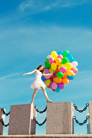 Happy birthday woman against the sky with rainbow-colored air balloons in her hands. sunny and positive energy of urban street. Young beautiful girl on the grass in the city. photo