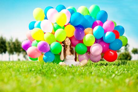 Alles Gute zum Geburtstag Frau gegen den Himmel mit Regenbogen-farbigen Luftballons in ihren Händen. sonnig und positive Energie der Natur. Junge schöne Mädchen auf dem Rasen im Park.
