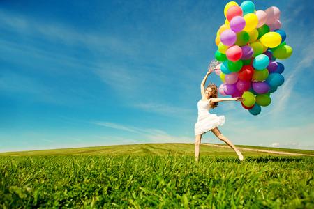 Alles Gute zum Geburtstag Frau gegen den Himmel mit Regenbogen-bunten Luftballons in den Händen. sonnig und positive Energie der Natur. Junge schöne Mädchen auf dem Rasen im Park. Standard-Bild - 26830214