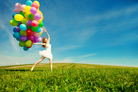 Gelukkige verjaardag vrouw tegen de hemel met regenboog-gekleurde lucht ballonnen in handen. zonnige en positieve energie van de natuur. Jong mooi meisje op het gras in het park.