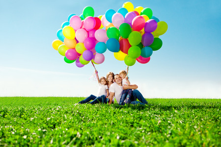 Happy family holding colorful balloons outdoor. Mom, ded and two daughters playing on  a green meadow.    Banco de Imagens