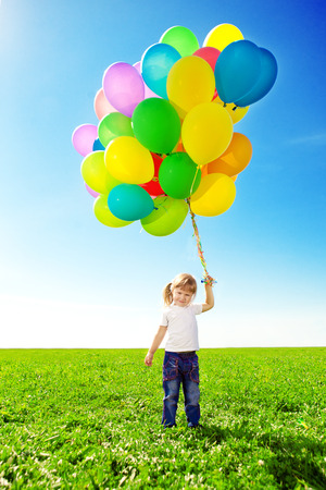 Happy little girl holding colorful balloons. Child playing on a green meadow. Smiling  kid.  photo
