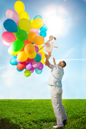 tosses: Father throws daughter. Familly playing together in park with balloons. Father tosses a baby against the sky