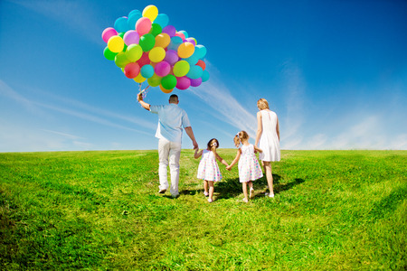 Happy family holding colorful balloons. Mom, ded and two daughters playing on a green  meadow. photo
