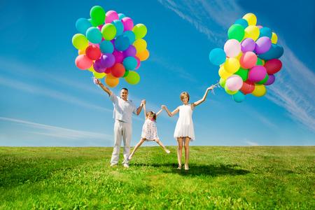 幸せな家族は、カラフルな風船を屋外に保有します。ママ、ded と二人の娘緑の草原で遊んで。