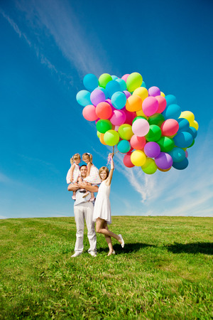 Happy family holding colorful balloons outdoor. Mom, ded and two daughters playing on a green meadow.