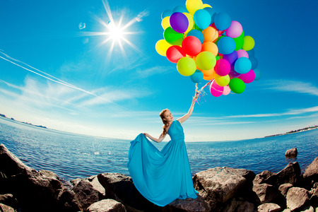 Luxury fashion woman with balloons in hand on the beach against the sky and the sun in long dress  Фото со стока