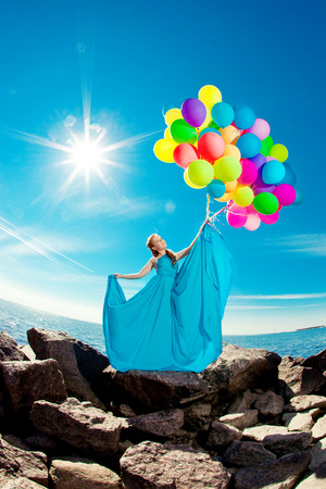 Luxury fashion stylish woman with balloons in hand on the beach against the sky and the sun in long dress photo