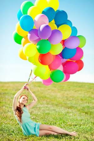 Luxury fashion stylish woman with balloons in hand on the field against the sky and  the sun in long dress  photo