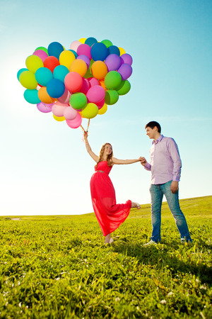 Young healthy beautiful pregnant woman with her husband and balloons outdoors. A Men  and girl with a tummy on the grass. Enjoyed by nature. Couple in love waiting for baby photo