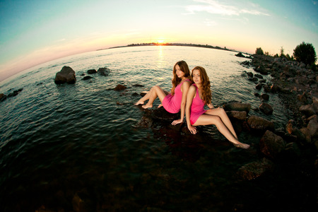 twin sister: Two beautiful women on the beach at sunset. Enjoy nature. Luxury girl relax by the  ocean. Stock Photo