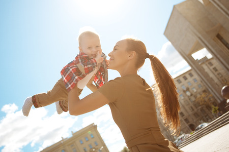 baby stroller: Trendy modern mother on a city street with a pram. Young mother walks with a child in the city. Beautiful young woman with a child in a baby carriage Stock Photo