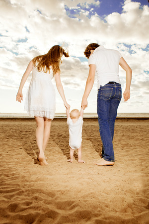 First steps of the kid. Happy family is helping baby takes first steps on the beach photo
