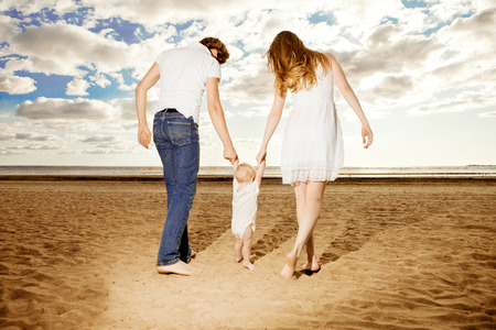 the first step: First steps of the kid. Happy family is helping baby takes first steps on the beach  Stock Photo