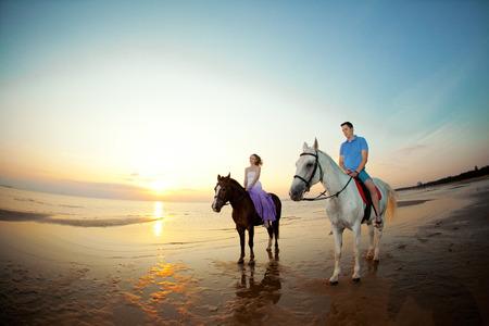 parapente: Dos jinetes a caballo al atardecer en la playa. Los amantes montan a caballo. Hermoso hombre joven y una mujer con un caballo en el mar. El amor romántico.