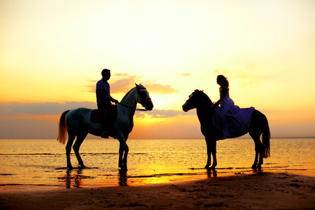 caballo de mar: Dos jinetes a caballo al atardecer en la playa. Los amantes montan a caballo. Hermoso hombre joven y una mujer con un caballo en el mar. El amor rom�ntico.