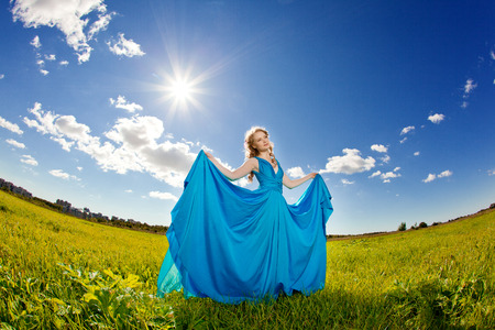 Luxury beautiful woman in long blue evening fashionable dress outdoors. In the  sunlight on a green field. photo