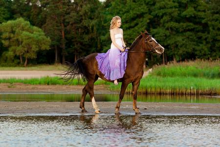 uomo a cavallo: Due cavalieri a cavallo al tramonto sulla spiaggia. Amanti passeggiata a cavallo. Giovane bella uomo e la donna con un cavallo al mare. L'amore romantico. Archivio Fotografico