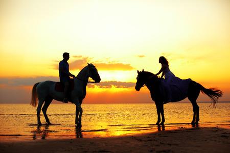 ビーチのサンセットで馬に乗って 2 人のライダー。馬の愛好家に乗る。海で馬を持つ女性、若い美しい男。ロマンチックな愛。 写真素材