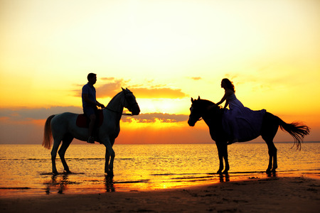 Two riders on horseback at sunset on the beach. Lovers ride horseback. Young beautiful  man and woman with a horses at the sea. Romantic love.