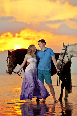 Two riders on horseback at sunset on the beach. Lovers ride horseback. Young beautiful  man and woman with a horse at the sea. Romantic love. photo