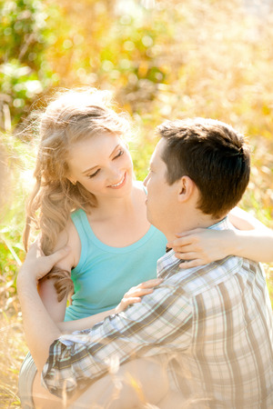 couples outdoors: Happy young adult couple in love on the field. Two,  man and woman smiling and resting on the green grass.