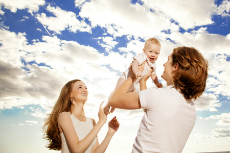 Happy family throws up baby boy against blue sky and white clouds photo