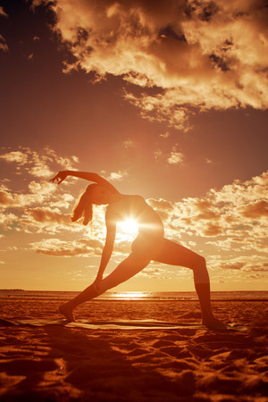 Young beautiful slim woman silhouette practices yoga on the beach at sunrise. Yoga at  sunset photo