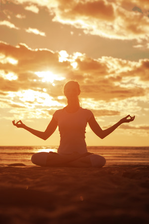 Junge schöne schlanke Frau Silhouette macht Yoga am Strand bei Sonnenaufgang. Yoga bei Sonnenuntergang Standard-Bild - 28320641