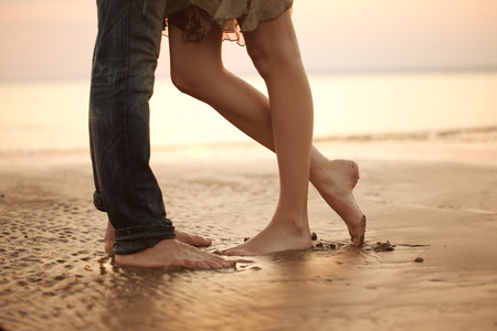 beach feet: A loving young couple hugging and kissing on the beach. Two lovers man and woman barefoot in the wet sand. Summer in love.