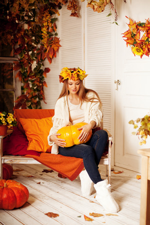 Beauty autumn woman smiling on the porch of yellow and orange autumn leaves. Stylish autumn girl