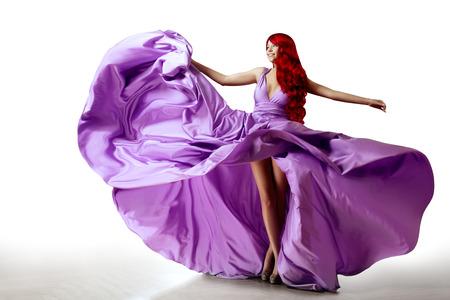 Luxury beautiful young woman in a long evening dress. Beauty girl in flying long silk dress Reklamní fotografie