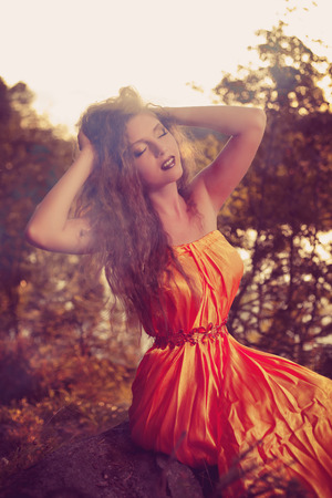 Beautiful witch in the woods near the fire. Magic woman celebrating Halloween.  photo