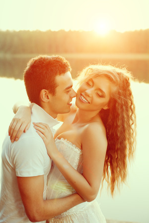 loves: Loving couple hugging on the lake. Beautiful young woman and man in the of the sun shining. Happy smiling Loves a date