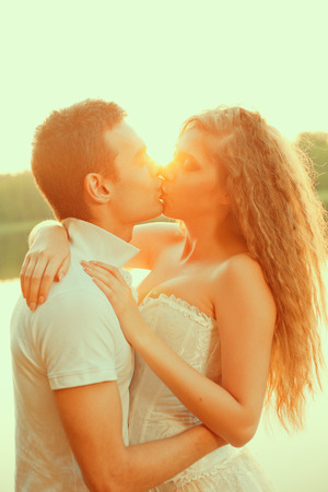 Loving couple hugging on the lake. Beautiful young woman and man in the of the sun shining. Happy smiling Loves a date photo