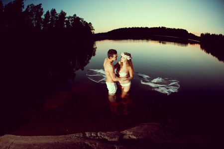 Two young lovers in a lake at night. Girl and man at sunset in the lake. photo