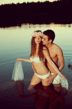 mystery man: Two young lovers in a lake at night. Girl and man at sunset in the lake.